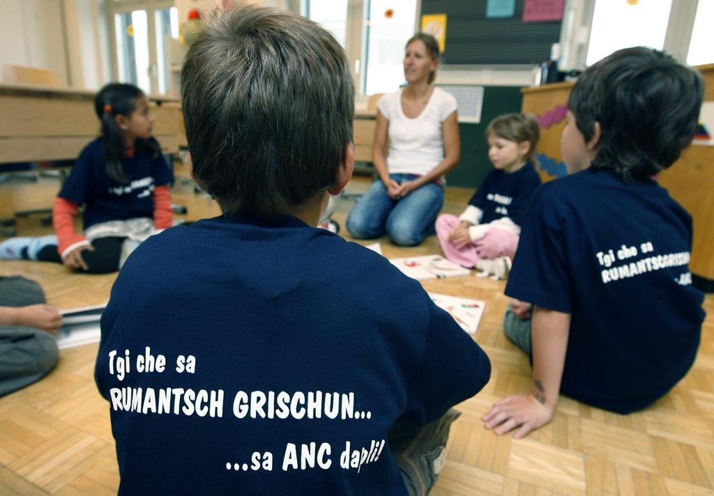 Scolars en scola cun il t-shirt tgi che sa rumantsch grischun... sa anc dapli.