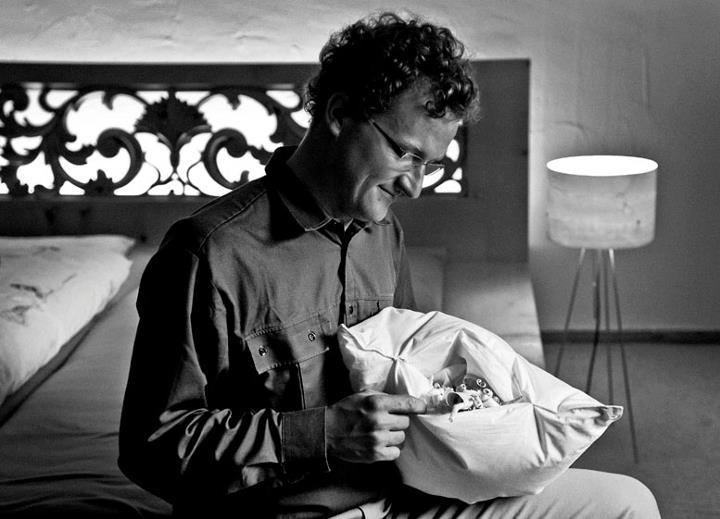 Il scrinari Marco Cadonau da S-chanf sesa sin in letg entaglià dad el, en maun in plimatsch cun en stalizzas da schember.