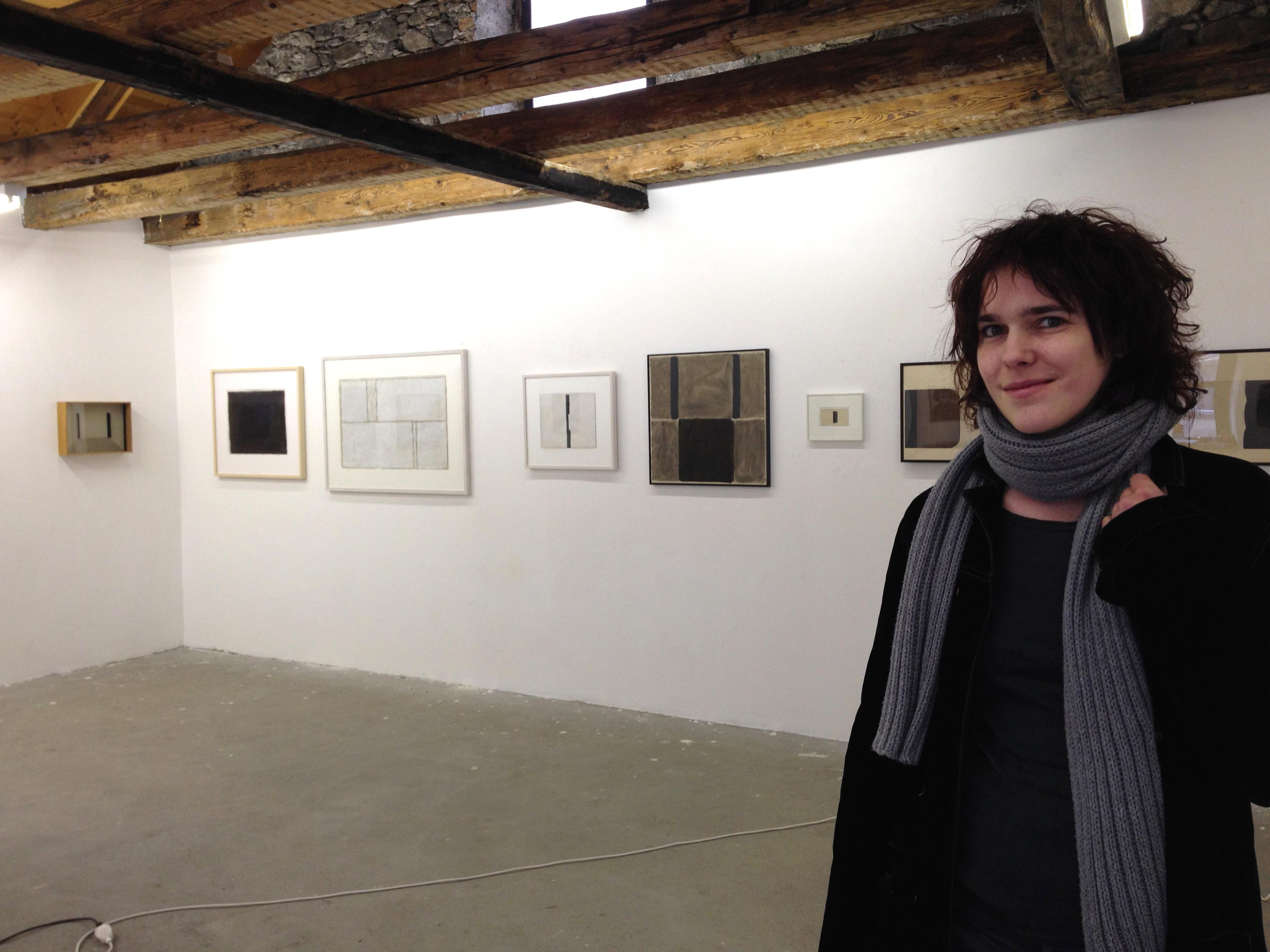 La curatura Ginia Holdener en la Galaria Fravi davant ils purtrets da l'artist Matias Spescha.