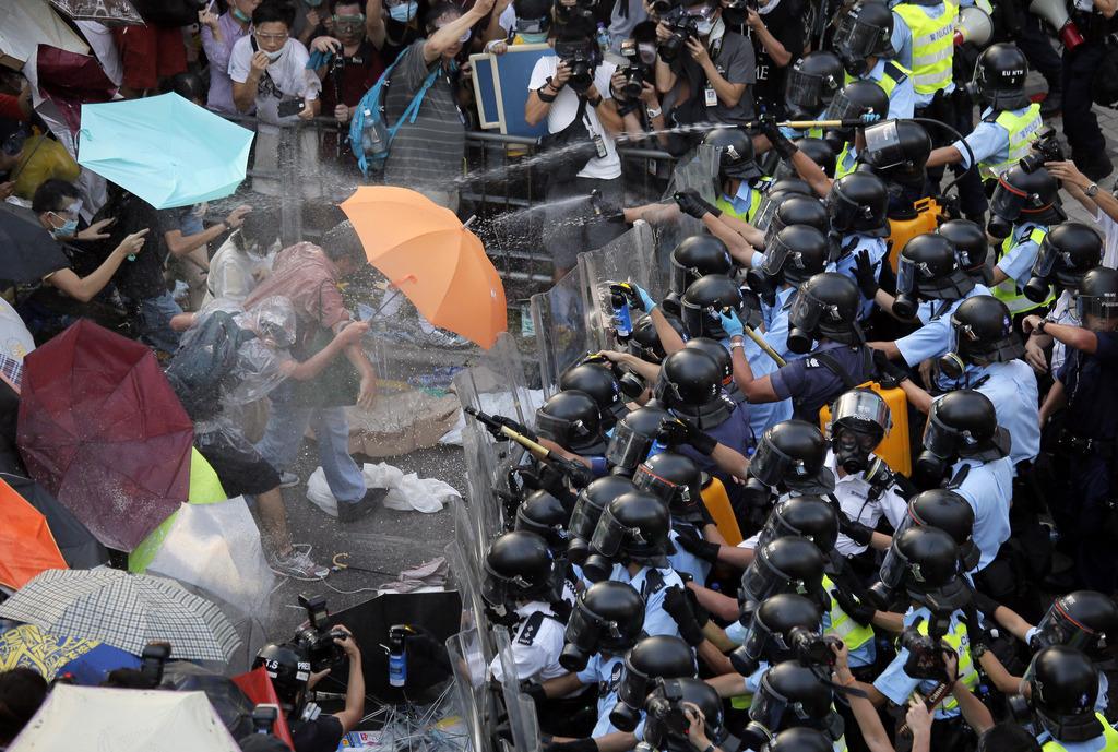 Ils demonstrants sa protegan cun parasols encunter la polizia.